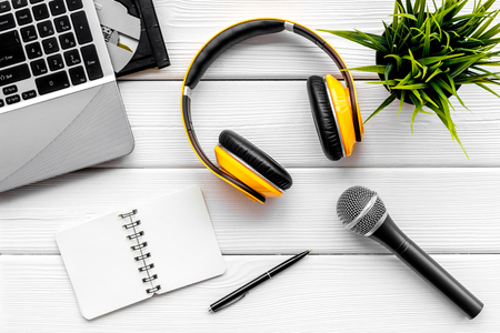 Record studio set. Blogger, journalist or musician work space with microphone, laptop and headphones on white wooden background top view space for text