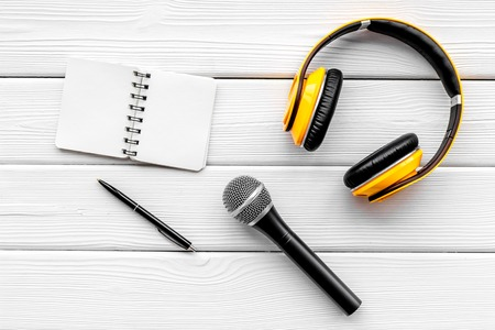 Record studio set. Blogger, journalist or musician work space with microphone, notebook and headphones on white wooden background top view mockup