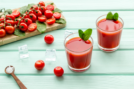 fresh drink with red tomato, spinach and ice on mint green background