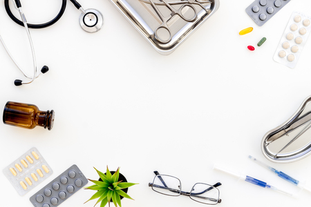 work desk of doctor in hospital with medical set on frame white background top view mockup
