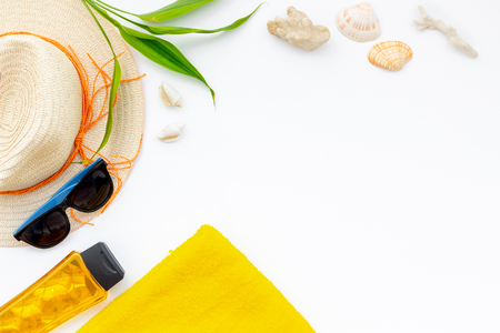 Straw hat, sun glasses, shells and sunblock cream for sea vacation on white background top view copy space