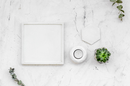 modern design of work desk with plant, candle on white marble background top view copy space