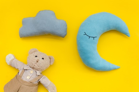 baby sleep pattern with moon pillow, cloud, teddy bear on yellow background top view