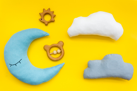 Baby care concept with moon pillow, clouds and toy for sleep of newborn on yellow background top view Stock Photo