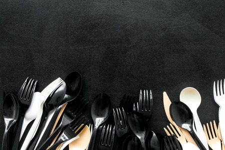 Eco and plastic utilization concept with flatware on black background top view mock up