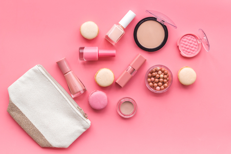 Beauty blogger work. Make-up artist desk with powder, nail polish, lipstick, blusher, bag, decorative cosmetics and macaroon cookies on pink background top view