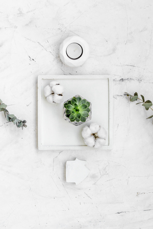 Plant, candle, concrete figures and tray decorations for modern home office design on marble work desk background flat lay