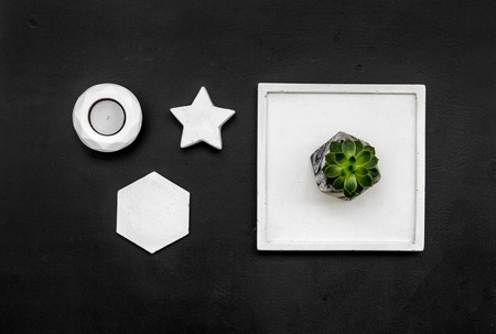 Home office. Work desk design with concrete decorations, candle and plant on black background top view Zdjęcie Seryjne