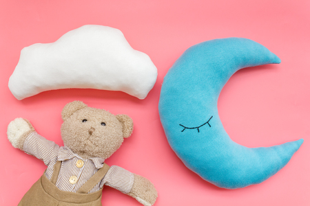 Baby care. Sleep of newborn. Put baby into bed with moon pillow, clouds, teddy bear and toy on pink background top view
