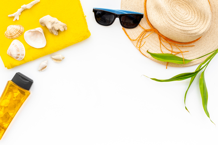 Travel to the seaside. Straw hat, sun glasses, shells and sunblock cream for sea vacation on white background top view copy space