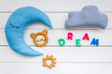 Baby care concept. Dream copy for baby pattern with moon pillow, cloud, toy on white wooden background top view