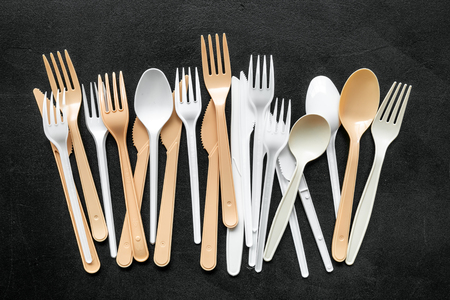 Plastic utilization and the Earth protection concept with flatware on black background top view Stock Photo