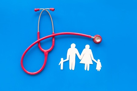 Family doctor desk with stethoscope and paper figures on blue background top view Фото со стока - 120861050