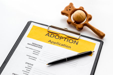Application to adopt child with toy on white background Stock Photo