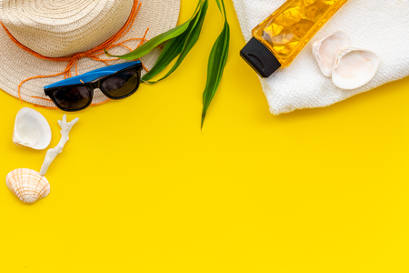 Summer traveling to the sea with straw hat, sun glasses, sunblock lotion on yellow background top view mock up Stockfoto