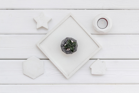 Plant, candle, concrete figures and tray decorations for modern home office on white wooden background flat lay