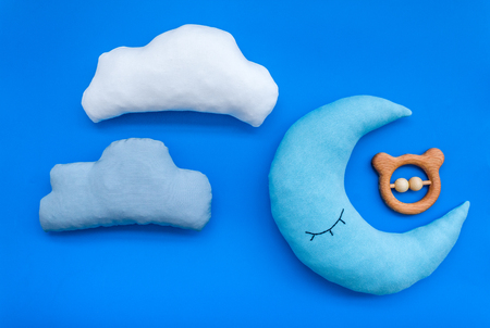 Put baby into bed with moon pillow, clouds and toy on blue background top view Stock Photo