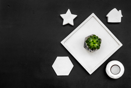 Work desk design with concrete decorations, candle and plant on black background top view space for text