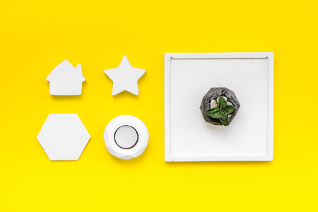 Home office. Work desk design with concrete decorations, candle and plant on yellow background top view