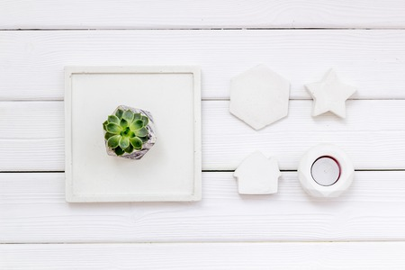 Home decoration. Modern design of work desk with plant, candle, house and star figures on white wooden background top view Zdjęcie Seryjne