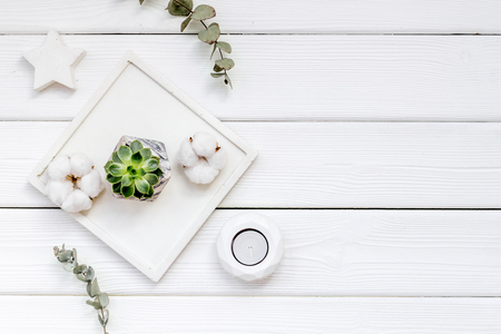 Home office. Work desk design with concrete decorations, candle and plant on white wooden background top view space for text