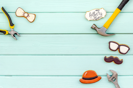 Bow tie, mustache, glasses, hat and instruments for repair for Happy Father Day party on mint green wooden background top view mockup Stock Photo
