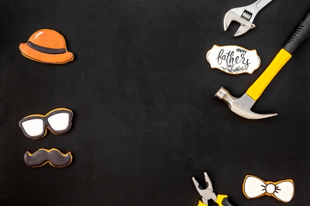 Bow tie, mustache, glasses, hat and instruments for repair for Happy Father Day party on black background top view mockup