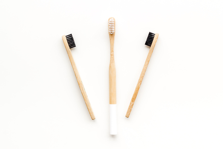 Bamboo dental cleaning brush for zero waste lifestyle concept on white background top view.