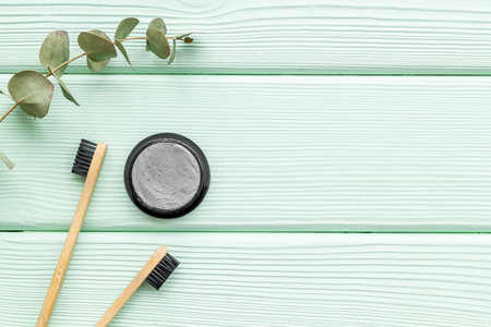 Bamboo dental cleaning brush and bamboo carbon toothpaste for zero waste lifestyle concept and care for teeth on mint green wooden background top view mockup