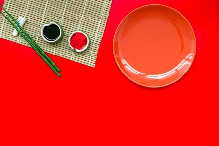 Bamboo sticks, soy sauce, ginger and dishes for sushi and maki cooking on red table background top view mockup