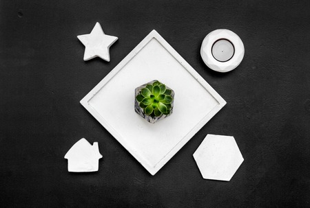 Home decoration. Modern design of work desk with candle, star figures on black background top view