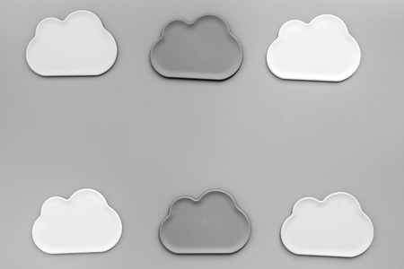 Cloud service concept with clouds figures on gray office desk background top view mockup