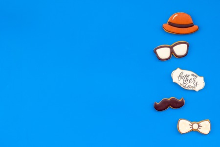 Bow tie, moustache, glasses and hat for Happy Father Day celebration party on blue background top view copy space.
