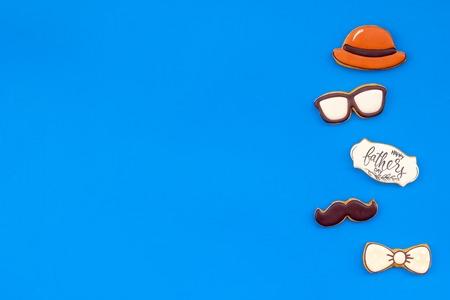 Fliege, Schnurrbart, Brille und Hut für Happy Father Day Feierparty auf blauem Hintergrund Draufsicht Kopienraum.