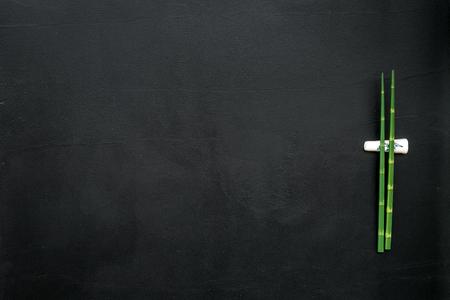 Tableau dressé. Cuisine asiatique sertie de bâtons de bambou pour sushi et maki sur fond noir vue de dessus maquette Banque d'images