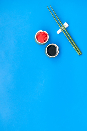 Bamboo sticks, soy sauce, ginger for sushi and maki cooking on blue table background top view mockup Stock fotó