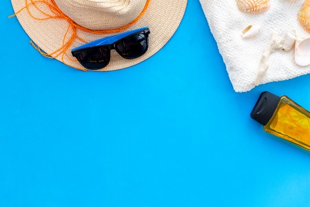 Planning vacation. Summer traveling to the sea with straw hat, sun glasses, shells and sunblock lotion on blue background top view mock up Stockfoto