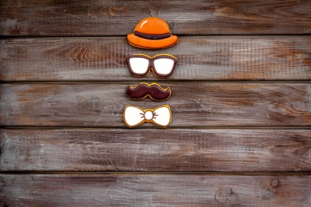 Bow tie, moustache, glasses and hat for Happy Father Day celebration party on wooden background top view copy space.