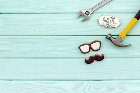 Bow tie, moustache, glasses and instruments for repair for Happy Father Day party on mint green wooden background top view mockup