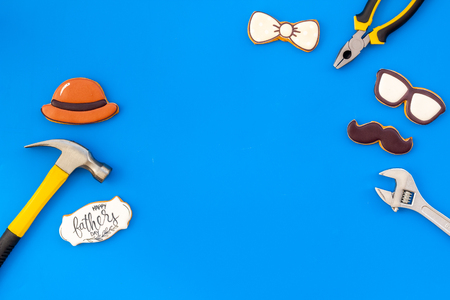Bow tie, moustache, glasses, hat and instruments for repair for Happy Father Day party on blue background top view mockup
