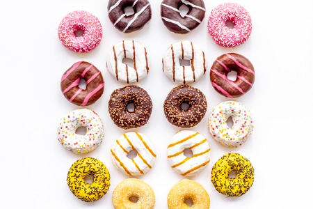Sweet break concept. Traditional american donuts of different flavors on white background flat lay pattern