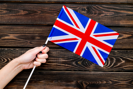 Flag of United Kingdom of Great Britain in hand on wooden background top view.