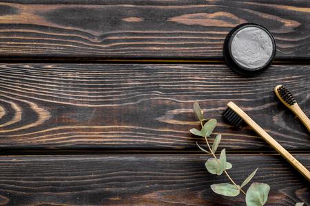 Cepillo de limpieza dental de bambú y pasta de dientes de carbón de bambú negro para un concepto de estilo de vida sin desperdicio y cuidado de los dientes en la maqueta de vista superior de fondo de madera