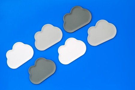 Cloud service concept with clouds figures on blue office desk background top view