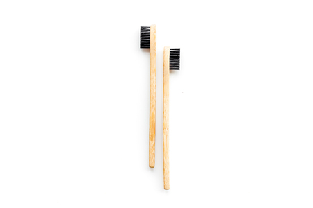 Bamboo dental cleaning brush for zero waste lifestyle concept on white background top view mock up.