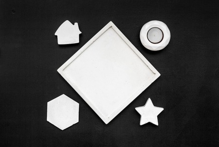 Candle, concrete figures and tray decorations for modern home office design on black work desk background flat lay mock up