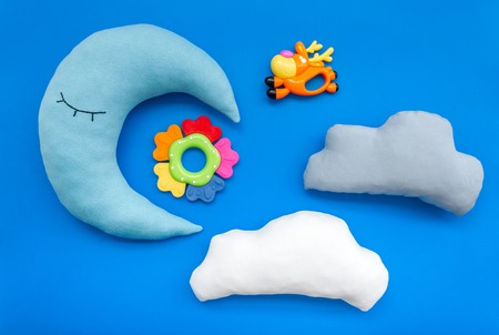 Baby care. Sleep of newborn. Put baby into bed with moon pillow, clouds and toy on blue background top view