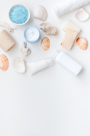 Spa organic cosmetics, cream, lotion, bath salt, soap with Dead Sea minerals and shells on white desk background flat lay space for text