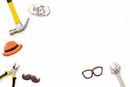 Moustache, hat, glasses, set of tools and cookie with copy for Happy Father Day celebration party on white background top view copy space