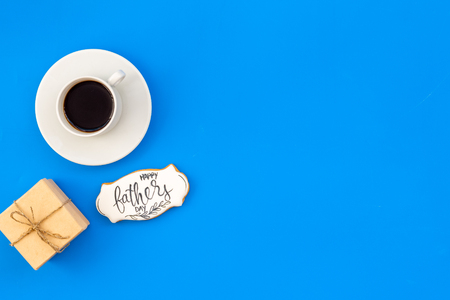 Cup of black coffee, box with gift and copy for Happy Father Day celebration party on blue background top view copy space